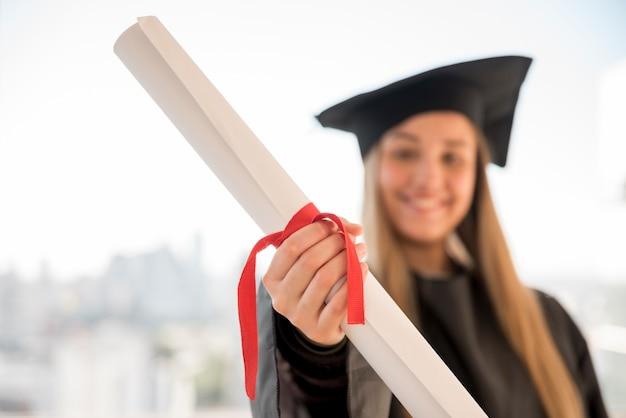 彼女の証明書のクローズアップを示す若い卒業生