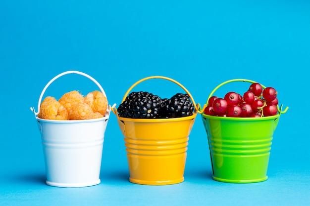 Крупный план маленьких ведер с ягодами