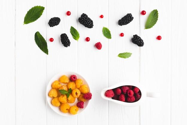 Плоская миска свежих ягод и листьев