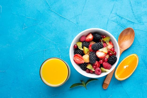 Плоская миска свежих ягод с соком и апельсинами