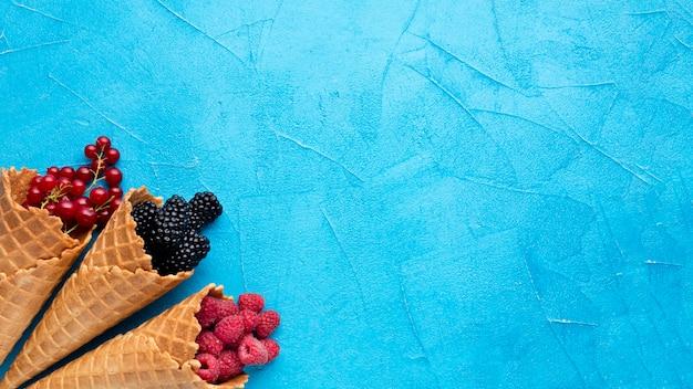 コピースペースを持つ果実とフラットレイアイスクリームコーン