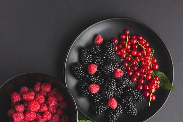 Плоская тарелка и миска свежих ягод