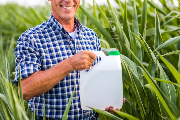 殺虫剤を保持している笑顔の男することができます。
