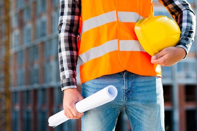 ヘルメットを保持しているクローズアップの建設労働者