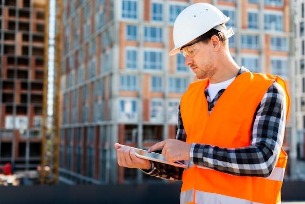 タブレットを使用してミディアムショットサイドビュー建設エンジニア