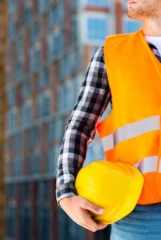 Крупный инженер-строитель держит шлем