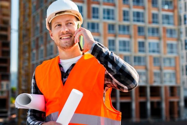 Средний снимок портрет инженер-строитель разговаривает по телефону
