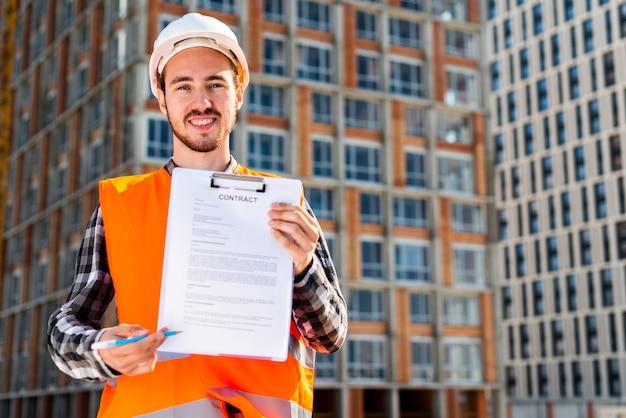 Средний снимок портрет строительного инженера, держащего контракт