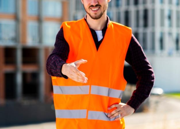 握手を提供しているクローズアップの建設労働者