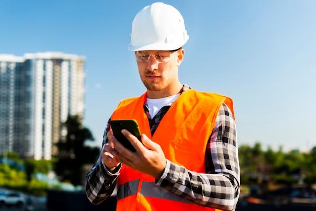 Средний снимок инженера, смотрящего на телефон