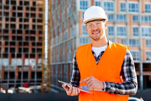 Средний снимок портрет улыбающегося инженера, глядя на камеру