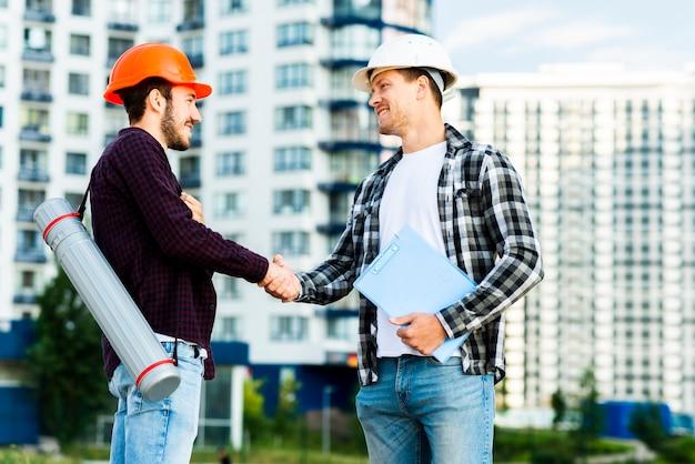 エンジニアと建築家の握手のミディアムショット
