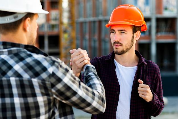 エンジニアと建築家の握手のクローズアップ