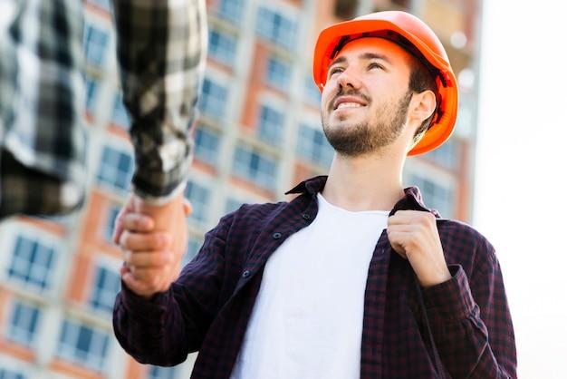 エンジニアと建築家の握手のクローズアップの低角度のビュー