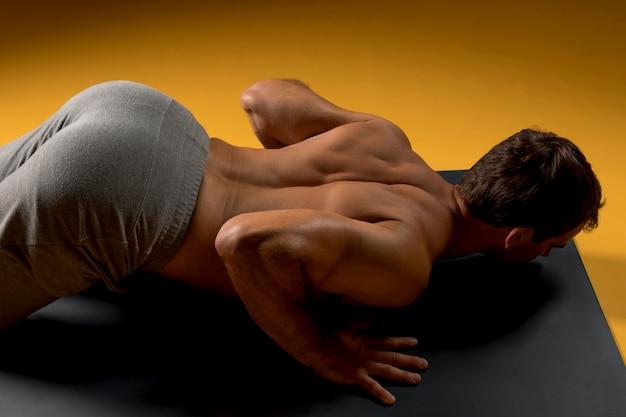 Человек взгляд сверху кладя на циновку йоги