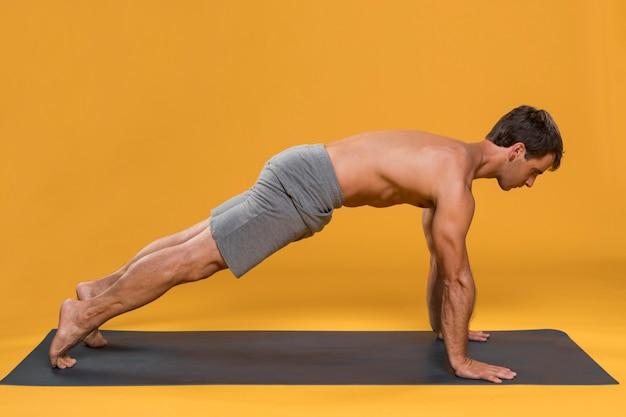 Человек тренируется на коврик для йоги