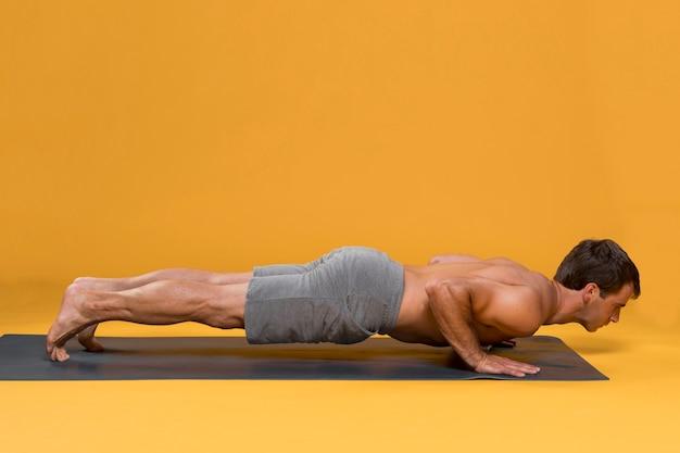 Человек делает отжимания на коврик для йоги