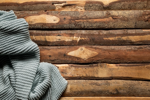 平らな木製の背景にかぎ針編みの毛布を置く