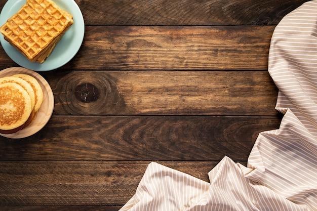 トップビューのパンケーキと縞模様のシートとワッフル