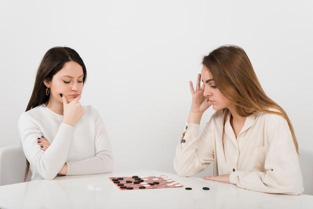 Друзья играют в шашки дома