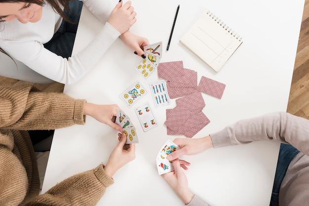 Вид сверху играющих в карты друзей