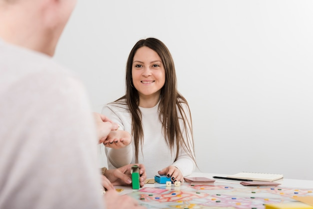 Вид спереди улыбается женщина играет в настольную игру
