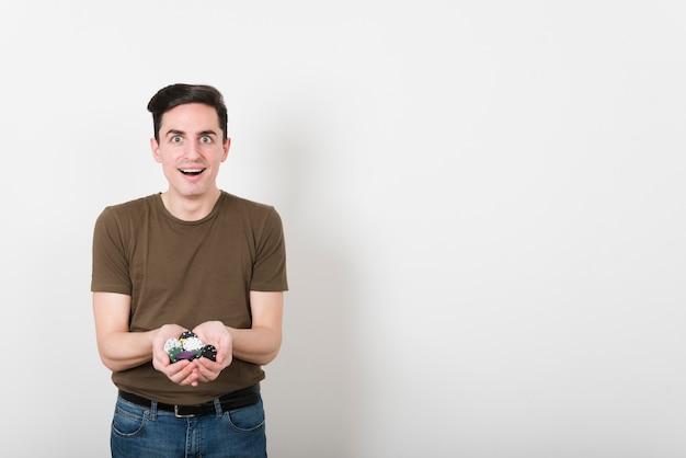 フロントビューポーカー用のチップを持つ幸せな男