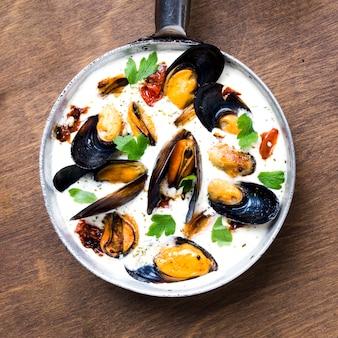 Плоская сковорода с мидиями в белом соусе