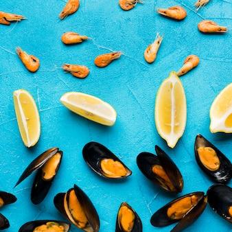Плоские вареные мидии и лимоны, разбросанные по столу