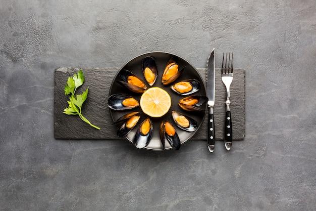 Плоская вареная тарелка с мидиями на грифельной доске