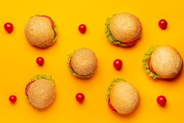 オレンジ色の背景を持つ平らな横になっているハンバーガー