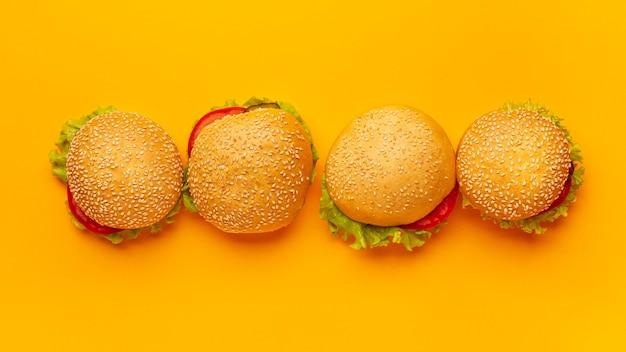Вид сверху гамбургеры с оранжевым фоном