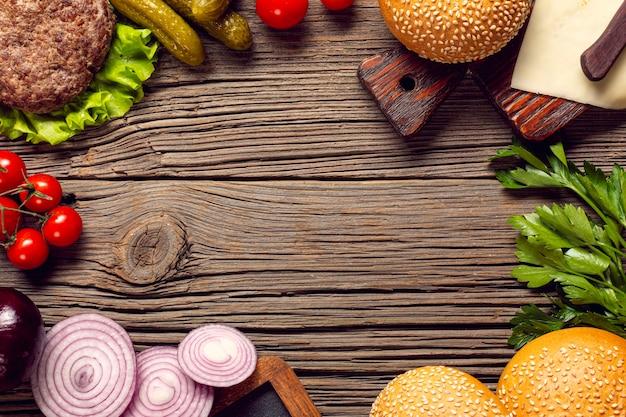 フラットレイアウトのハンバーガーの食材を木製のテーブル