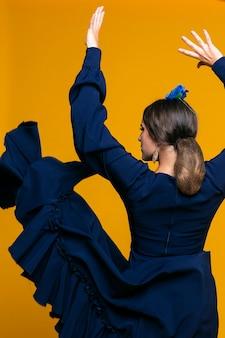 オレンジ色の背景と手を上げる背面図若い女性