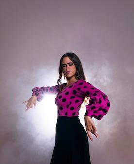 背中に光で踊るブルネットの女性