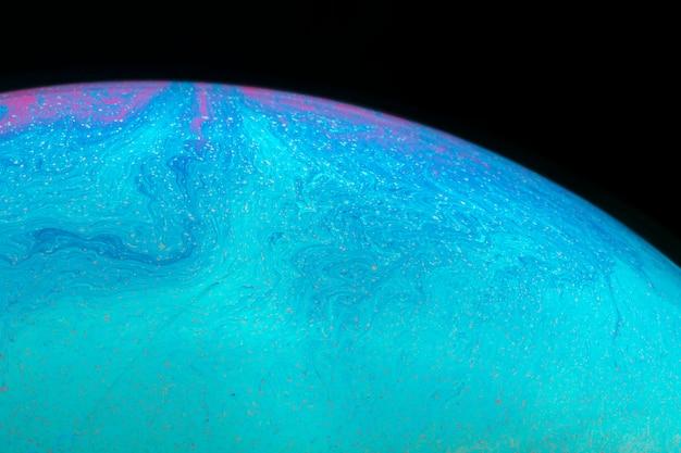 黒の背景に抽象的な色合いの波状シャボン玉
