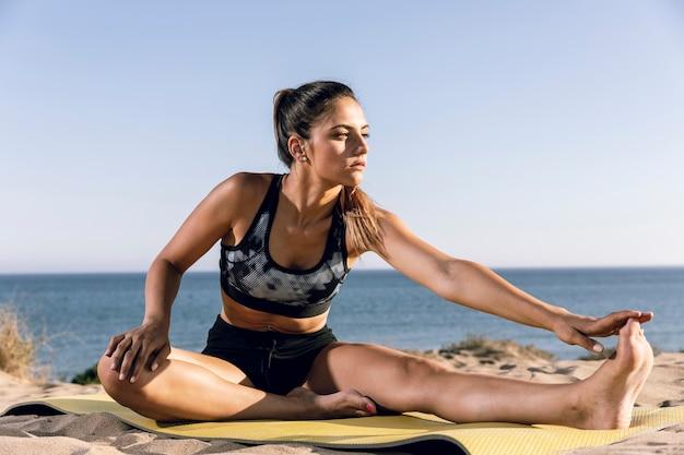 スポーティな女性がビーチでウォーミングアップ