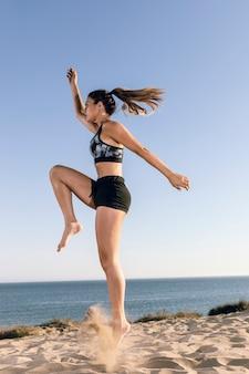 横にスポーティな女性が砂の上をジャンプ