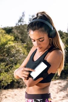 Женщина на пробежке ставит музыку на макет своего телефона