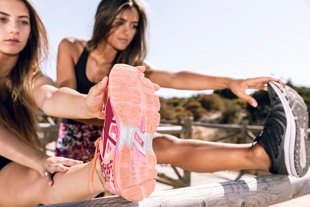 ミディアムショットの女性が桟橋で自分の足を伸ばして