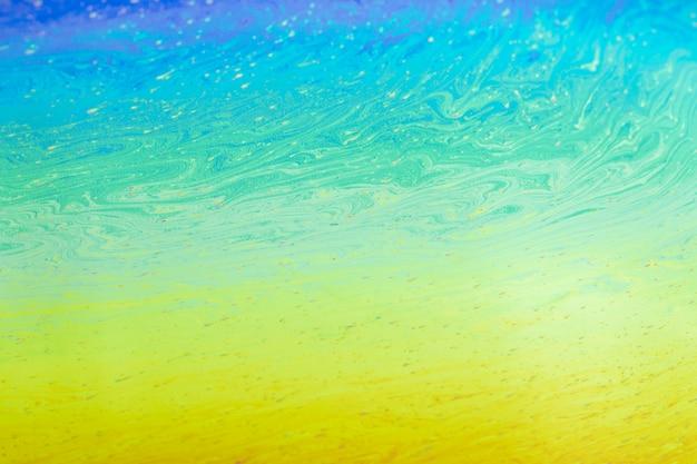 きらめく波状の青い緑と黄色の抽象的な背景