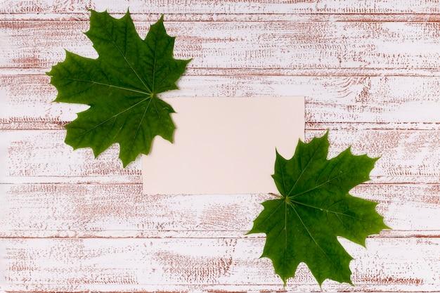 カエデの葉の木製の机の上のモックアップ
