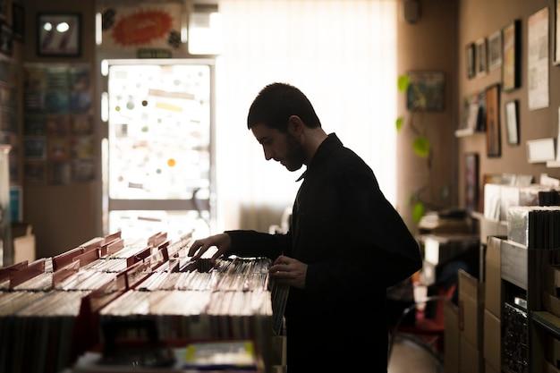店でビニールを探している若い男のミディアムショット側面図