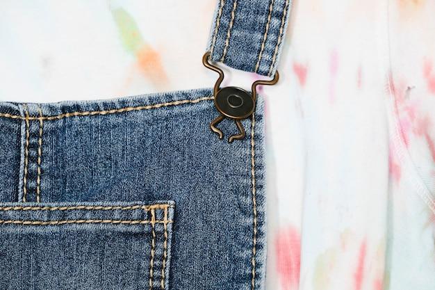 Верхняя часть синего джинсового комбинезона крупным планом