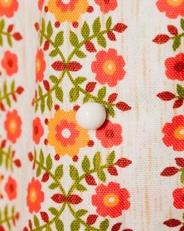 Блузка с цветами и белая пуговица крупным планом