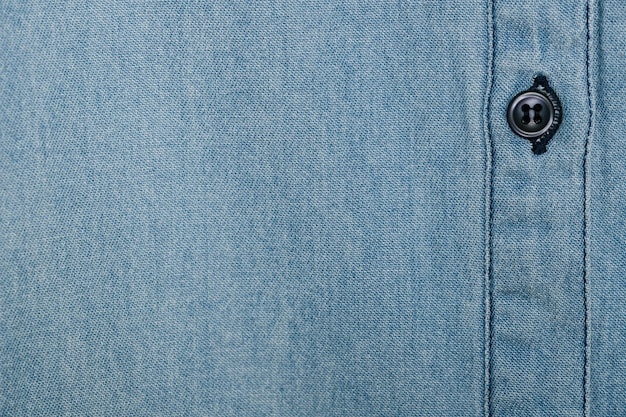 Голубая джинсовая рубашка с черной пуговицей