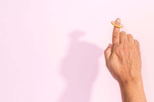 Рука крупным планом с презервативом на указательном пальце
