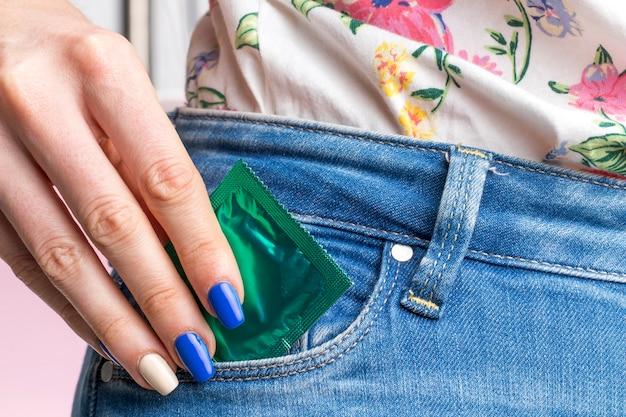 Крупным планом женщина с презервативом в кармане