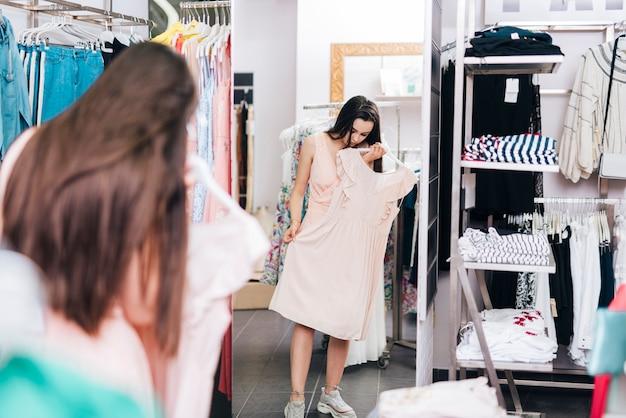 フルショットの女性がドレスを試着