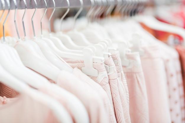Крупным планом розовые одежды на вешалках